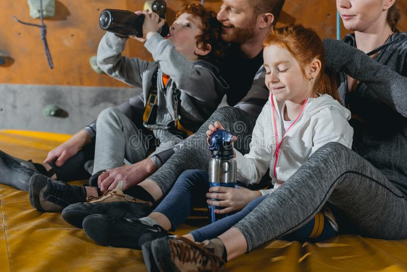 Family with children sitting on a mat at gym with climbing walls. In the background stock images