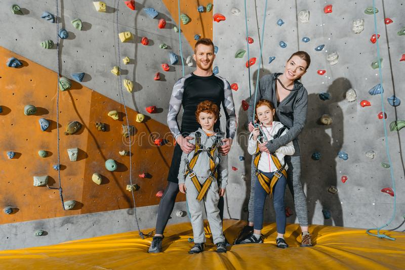 Family with children standing together near climbing walls at gym and looking. At camera stock photography