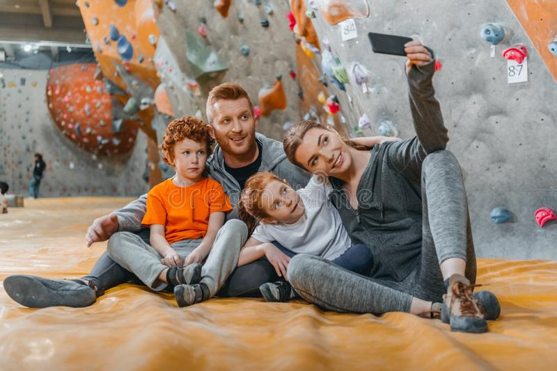 Family with children taking a selfie with smartphonesitting on a mat at gym. Near climbing walls royalty free stock photography