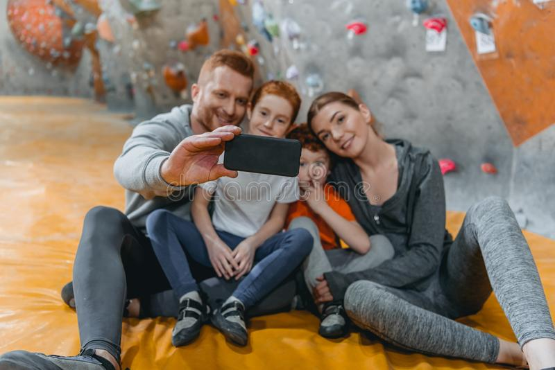 Family with children taking a selfie with smartphonesitting on a mat at gym. Near climbing walls royalty free stock images