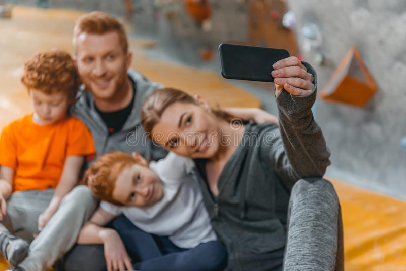Family with children taking a selfie with smartphonesitting on a mat at gym. Near climbing walls stock photo