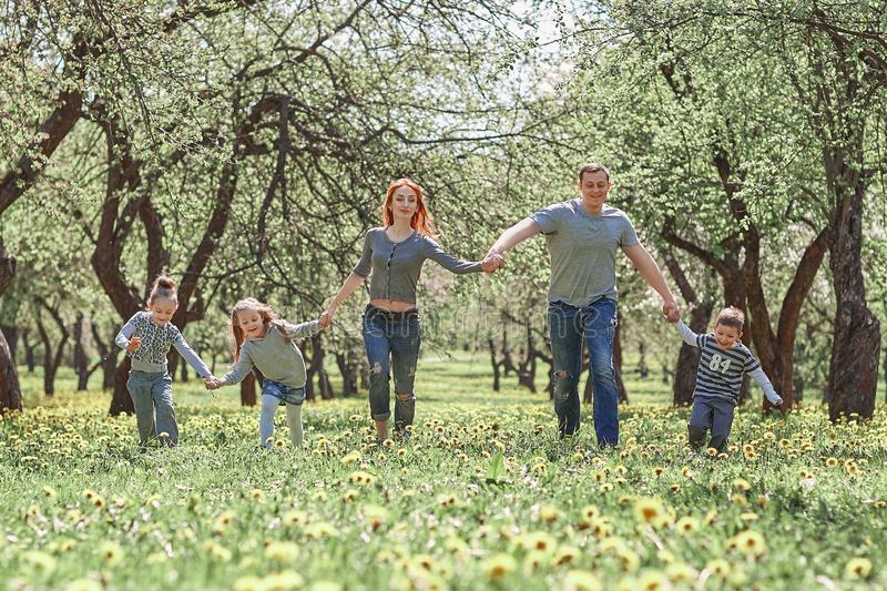 Family with children walking on the grass in the spring garden stock photography