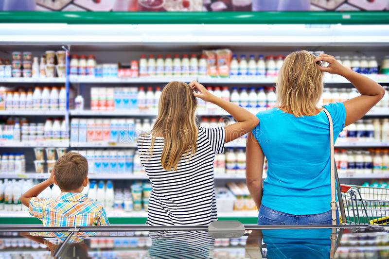 Family chooses dairy products in shop royalty free stock image