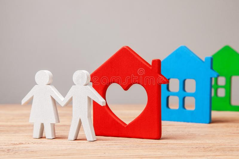 Family chooses house to buy or rent. Couple of man and woman and colorful houses royalty free stock image