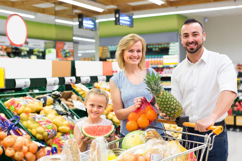 Family choosing fruits in hypermarket. Cheerful smiling parents with little daughter choosing fruits in hypermarket royalty free stock photography