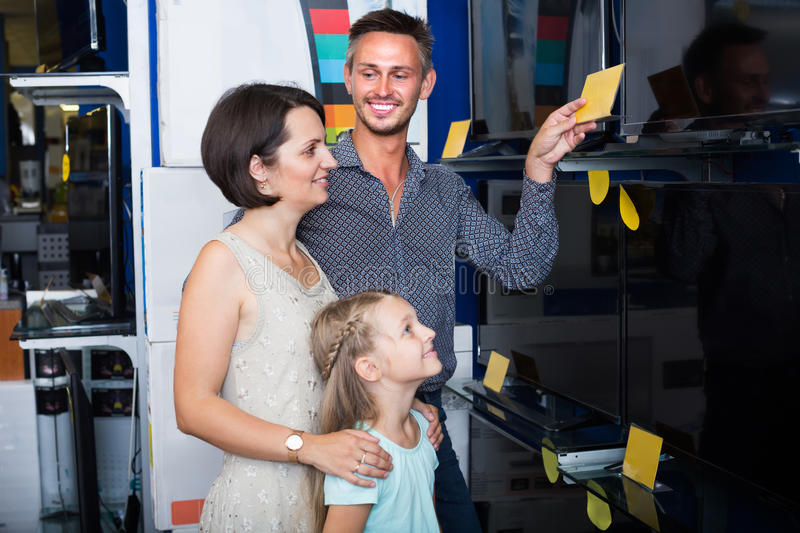 Family choosing new TV in store. Joyful smiling couple with little daughter buying new TV in shop of household appliances . Focus on man royalty free stock images
