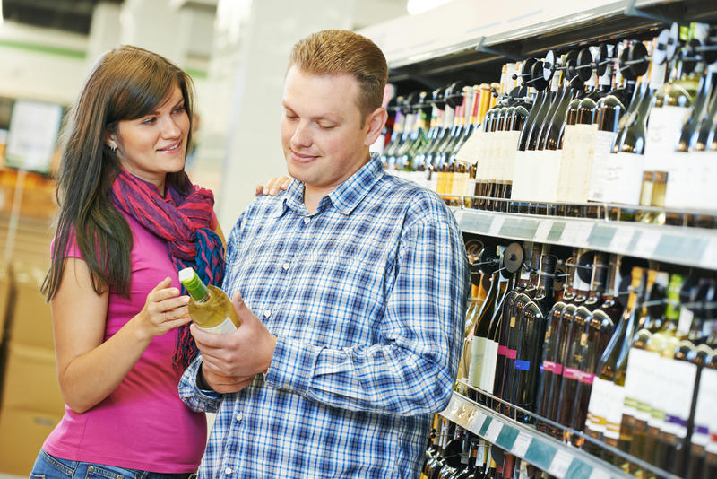 Family choosing wine in supermarket royalty free stock image