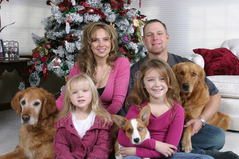 Family Christmas. Smiling family and dogs sitting by Christmas tree