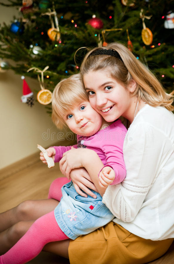 Family Christmas. Scene with two young girls sitting under the xmas tree together stock image