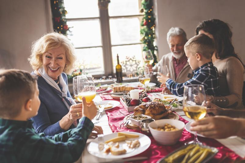 Family Christmas dinner toast. Happy family celebrating Christmas, having dinner at home, making a toast with glasses of wine and orange juice and enjoying their royalty free stock image