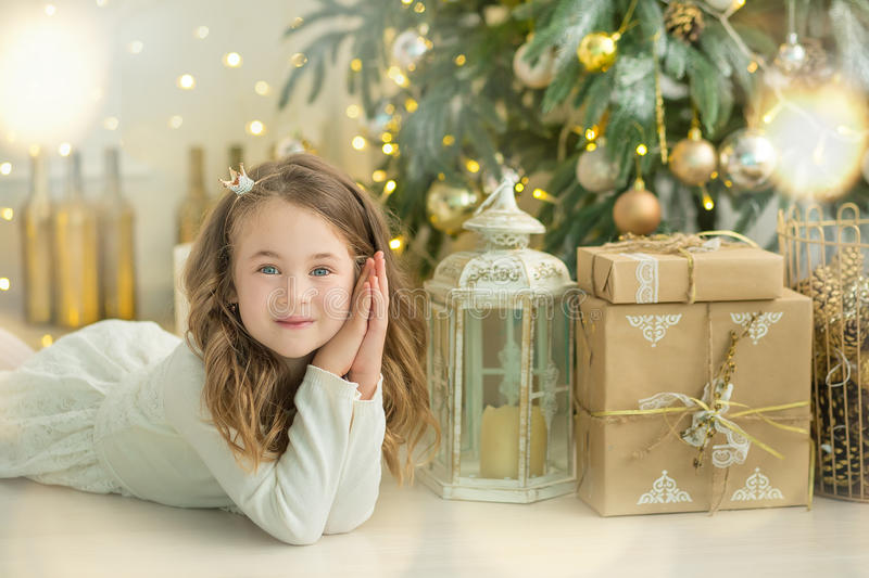 Family on Christmas eve at fireplace. Kids opening Xmas presents. Children under Christmas tree with gift boxes. Decorated living. Room with traditional fire royalty free stock photo