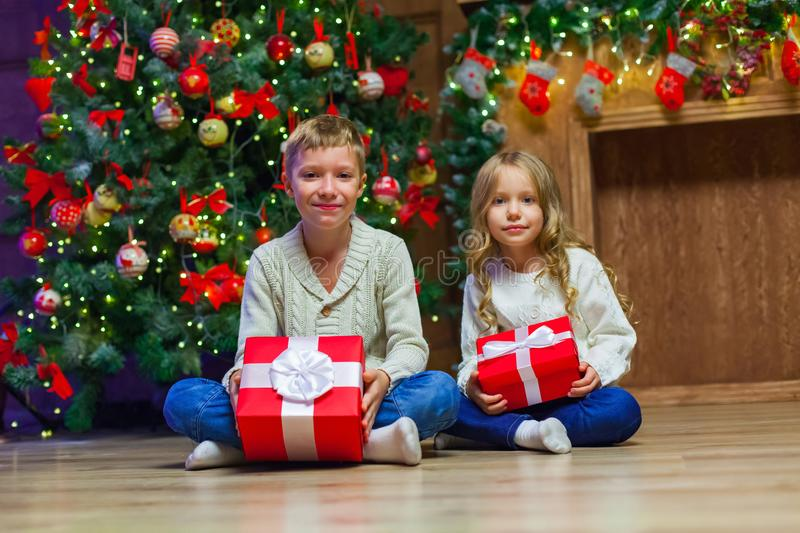 Family on Christmas eve at fireplace. Kids opening Xmas presents. Children under Christmas tree with gift boxes. Decorated living room with traditional fire royalty free stock photography