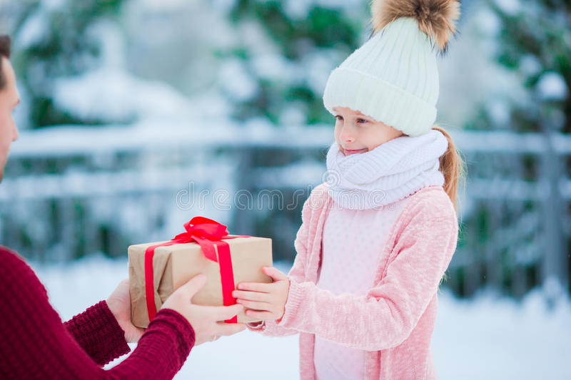 Family with Christmas gift on Xmas eve outdoors. Cute little girl with christmas box gift in winter day royalty free stock image