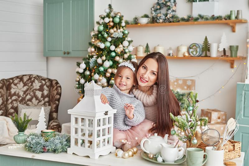 Family at Christmas in kitchen. Merry Christmas and Happy Holidays. Family preparation holiday food. Mother and daughter cooking C. Hristmas cookies.Kitchen stock photography