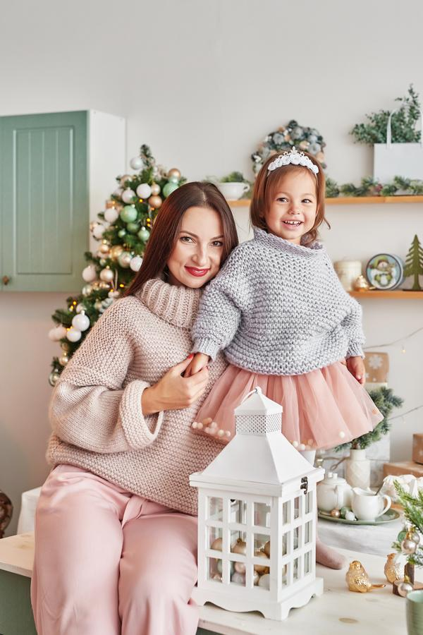 Family at Christmas in kitchen. Merry Christmas and Happy Holidays. Family preparation holiday food. Mother and daughter cooking C. Hristmas cookies.Kitchen royalty free stock image