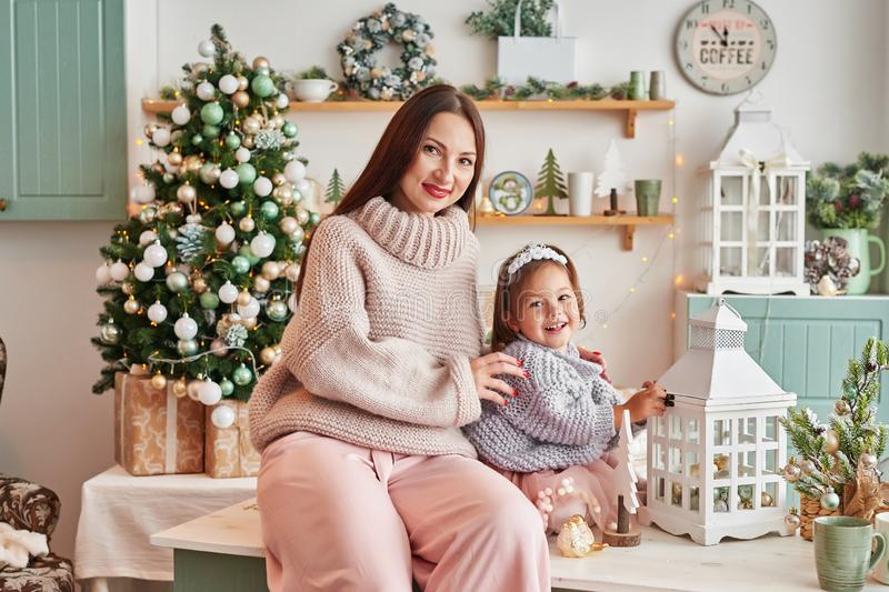 Family at Christmas in kitchen. Merry Christmas and Happy Holidays. Family preparation holiday food. Mother and daughter cooking C. Hristmas cookies.Kitchen royalty free stock photography