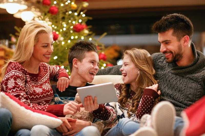 Family, Christmas, x-mas, technology and people concept - watching funny video on digital tablet. Family, Christmas, x-mas, technology and people concept stock photo
