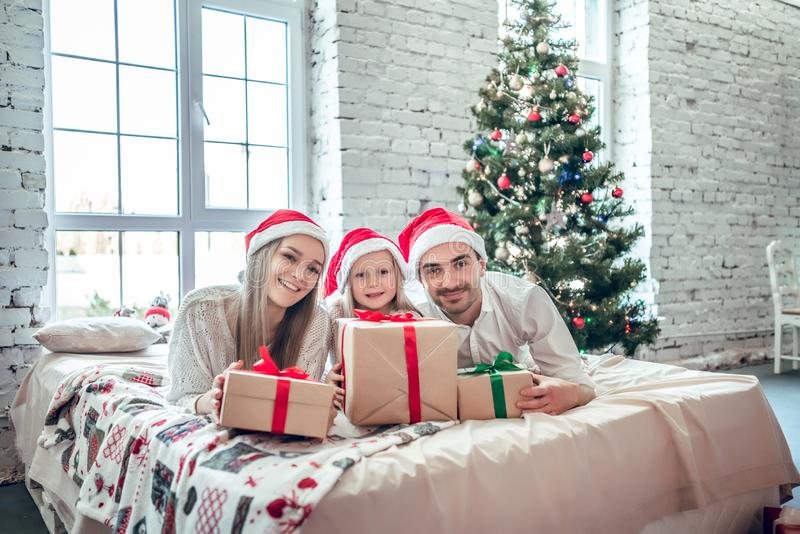 Family in Christmas Santa hats lying on bed. Mother father and baby having fun in bedroom. People relaxing at home. Winter holiday Xmas and New Year concept stock photography