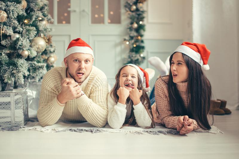 Family in Christmas Santa hats lying on bed. Mother father and baby having fun royalty free stock photo