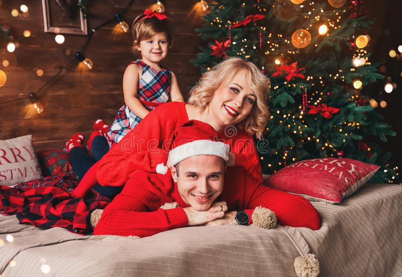 Family in Christmas Santa hats lying on bed. Mother, father and baby having fun in living room decorated by Christmas tree. And present gift boxes. New Year and royalty free stock images