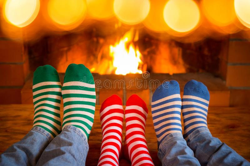 Family in Christmas socks near fireplace. Mother; father and child having fun together. People relaxing at home. Winter holiday Xmas and New Year concept royalty free stock image
