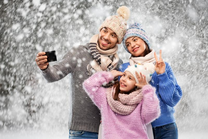 Happy family taking selfie by smartphone over snow stock photo