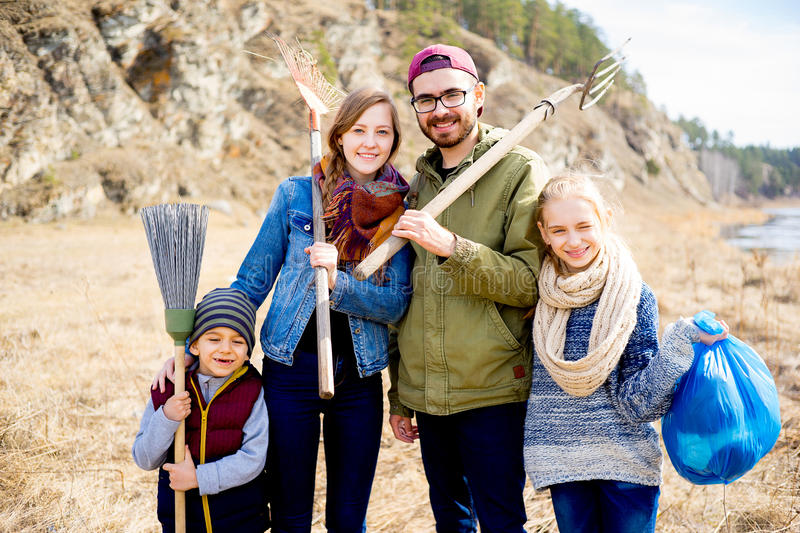 Family is cleaning outside. A happy family of four is cleaning outside royalty free stock photo