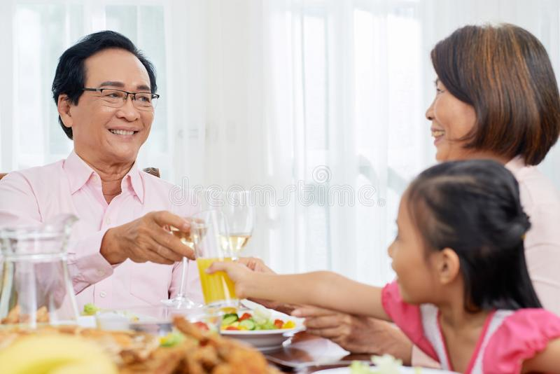 Family clinking with glasses at table royalty free stock photos