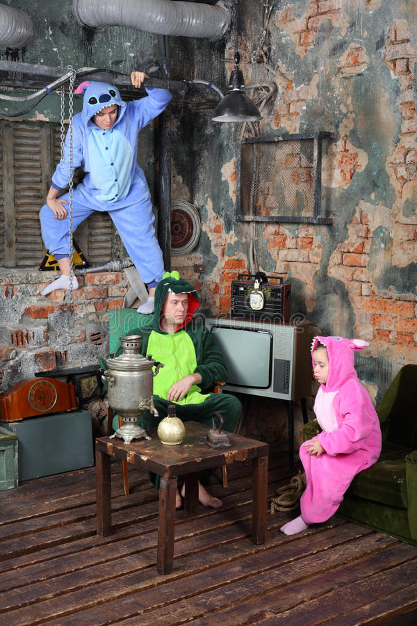 Family in colorful carnival costumes in very old room. With television and table with samovar stock photos