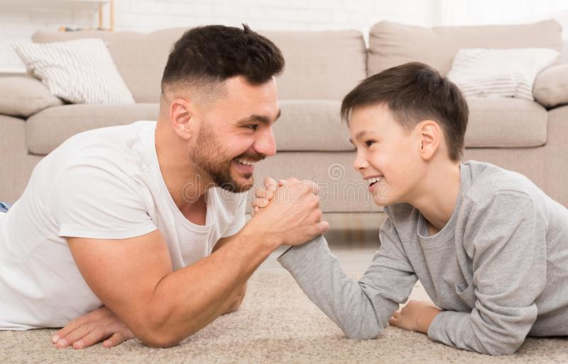 Father and son compete in arm-wrestling, lying on floor at home. Family competition. Father and son compete in arm-wrestling, lying on floor at home, panorama royalty free stock photos