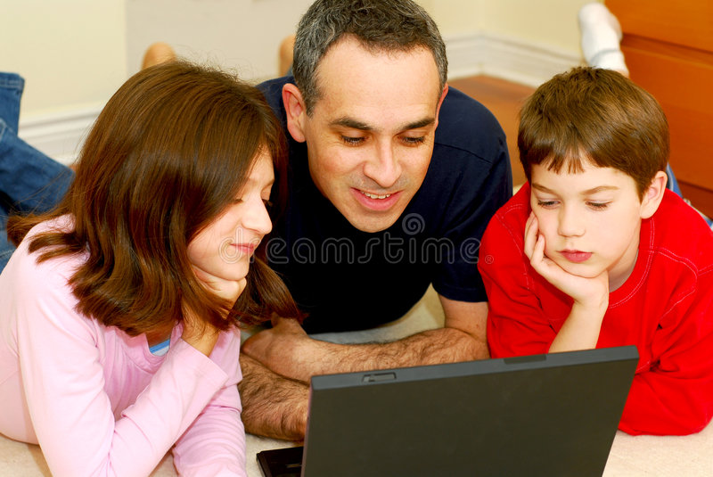 Family computer. Father and children lying on the floor at home and looking into a portable computer