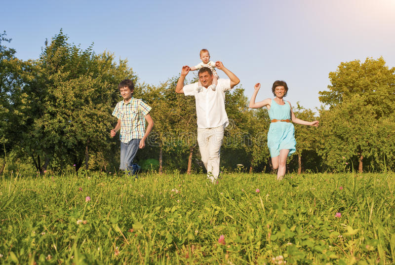 Family Concept and Ideas. Happy Family of Four Running Together. Outside in Green Summer Forest. Horizontal Image Orientation stock image