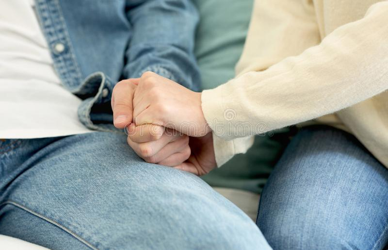 Family concept. Loving couple holding hand together. Sitting on sofa royalty free stock image