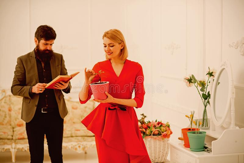 Family concept. Family of woman and man at home. Sensual woman hold green plant while bearded man reading book, family royalty free stock photos