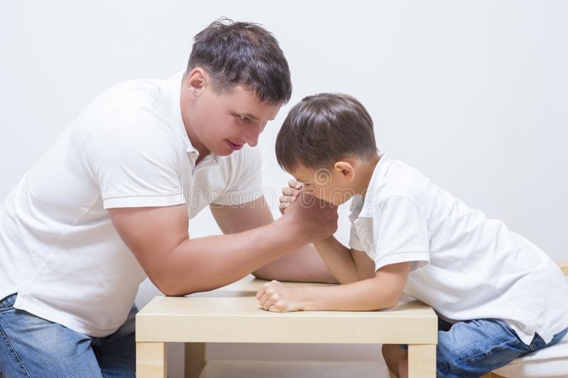 Family Concepts. Father is Having Armwrestling Tournament. Family Concepts. Father is Having Funny Armwrestling Tournament with His Little Son Indoors stock photography