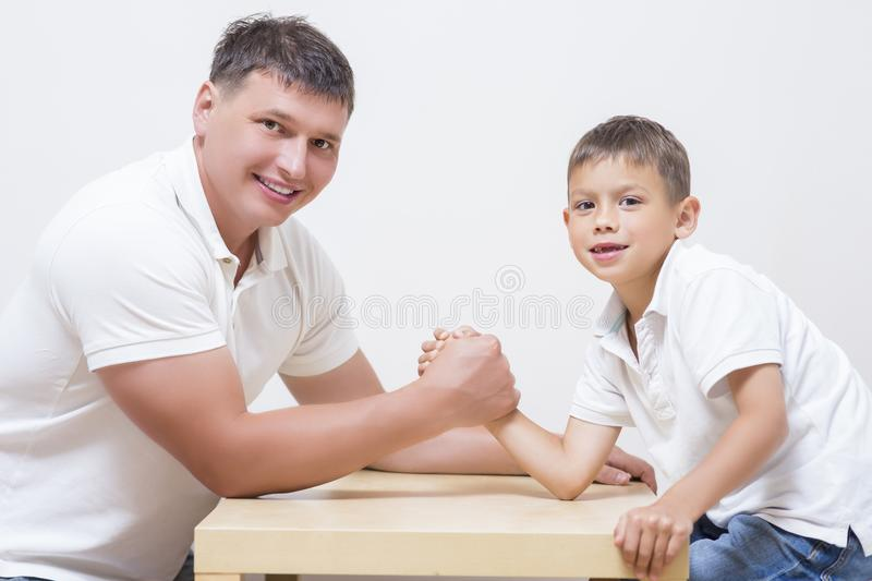 Father is Having Funny Armwrestling Tournament. Family Concepts. Father is Having Funny Armwrestling Tournament with His Little Son Indoors. Horizontal Image stock images