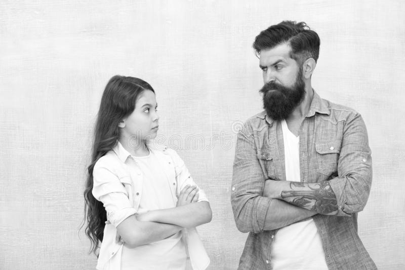 Family conflict. Bearded hipster man and child girl. Confrontation concept. Frowning man and serious daughter. Solving stock image