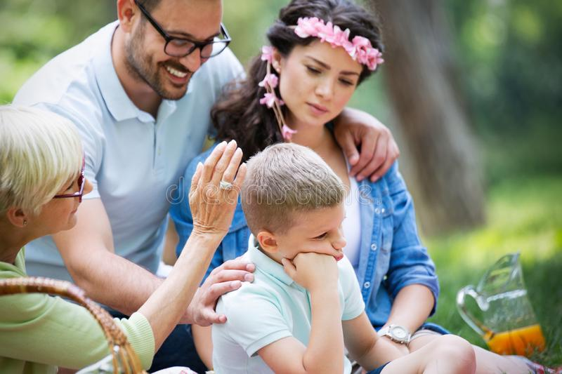 Family consoling little stubborn child and managing emotions. Outdoor royalty free stock image