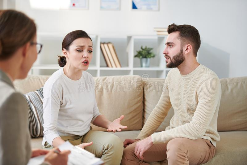Family consultation. Young emotional wife explaining problem in relationship with husband to their counselor at session stock photo