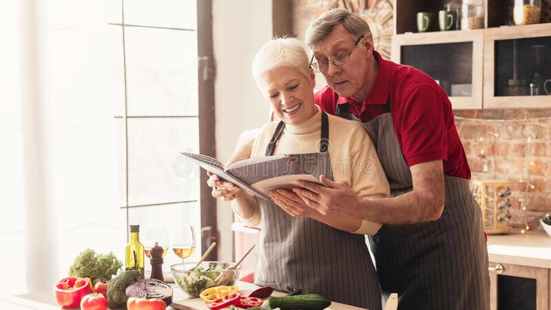Senior couple reading recipes at kitchen interior, panorama stock image