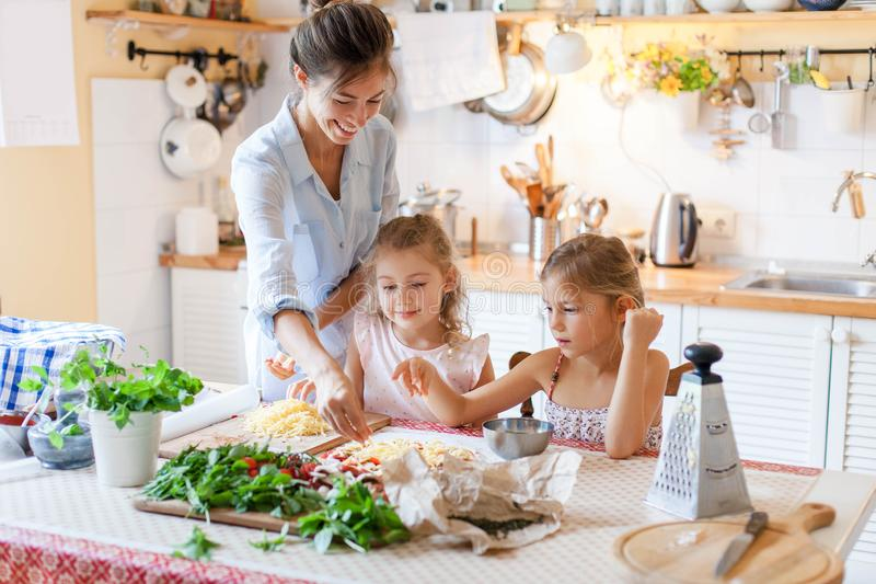 Family are cooking italian pizza together in cozy home kitchen. stock photography