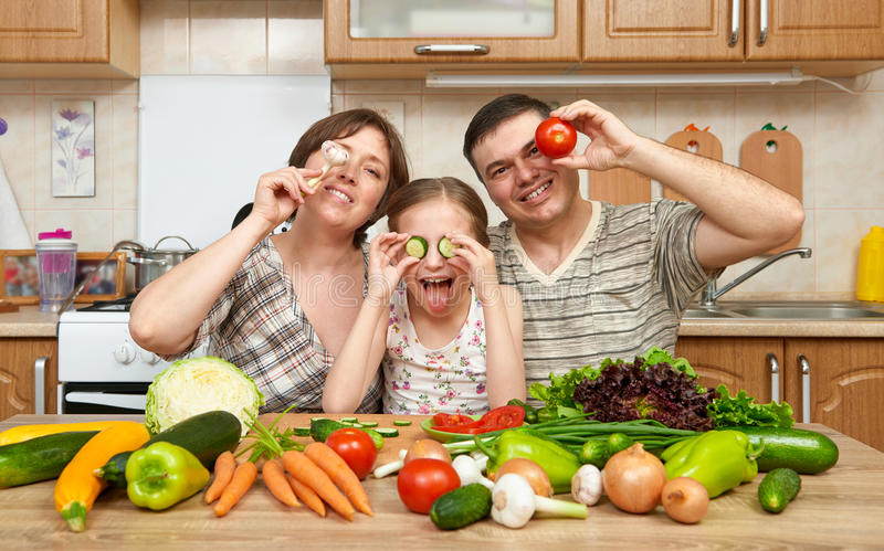 Family cooking in kitchen interior at home, fresh fruits and vegetables, healthy food concept, woman, man and children royalty free stock photography