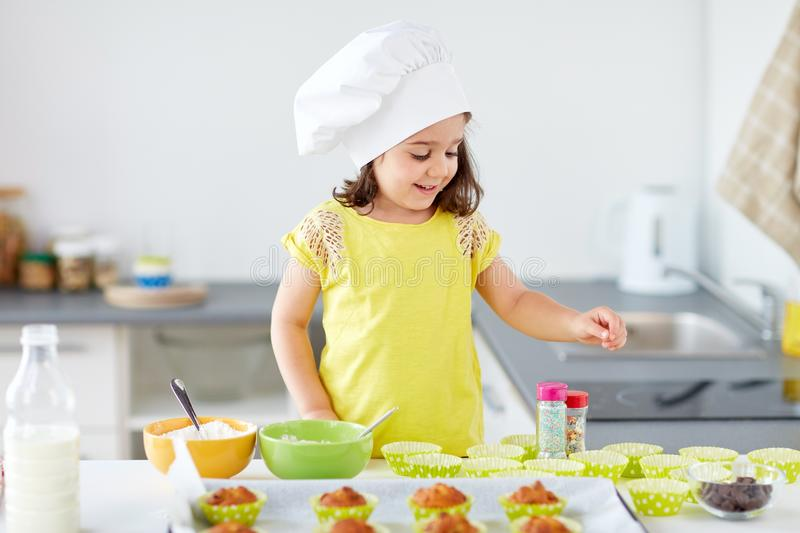 Little girl in chefs toque baking muffins at home. Family, cooking and people concept - little girl in chefs toque baking muffins or cupcakes with sprinkles at stock images