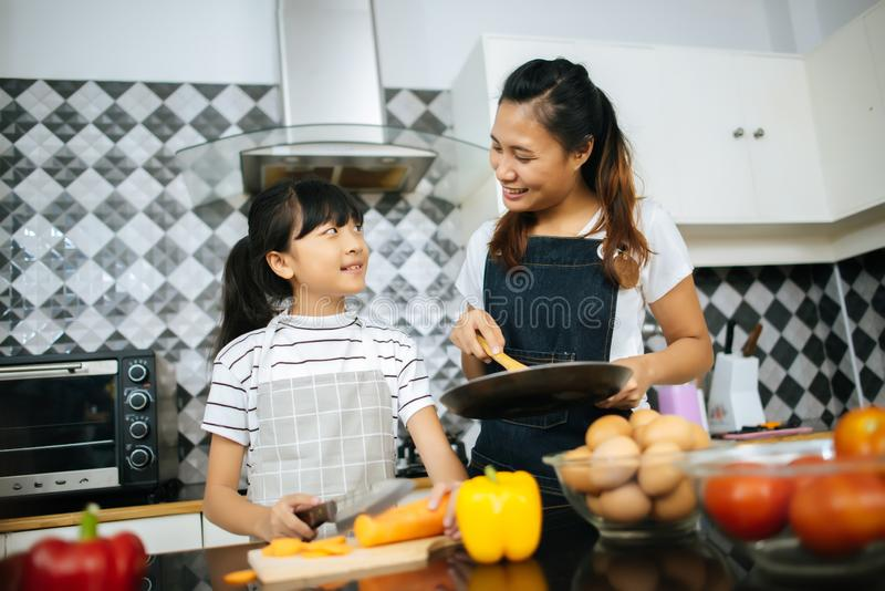 Family cooking time : Happy family help cooking meal together in kitchen royalty free stock image