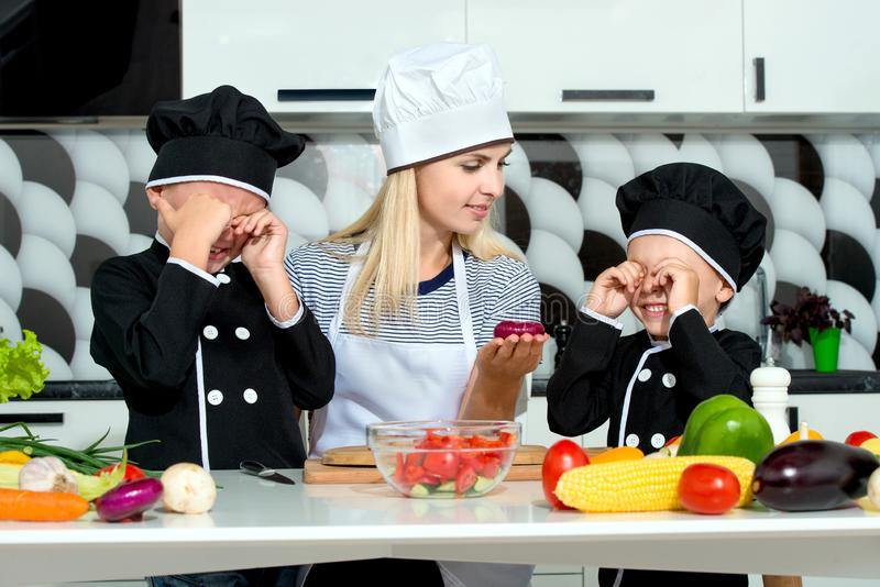A family of cooks.Healthy eating. Happy family mother and children prepares vegetable salad in kitchen royalty free stock photos