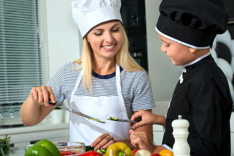 A family of cooks.Healthy eating.Mother and son prepares vegetable salad in kitchen. stock photo
