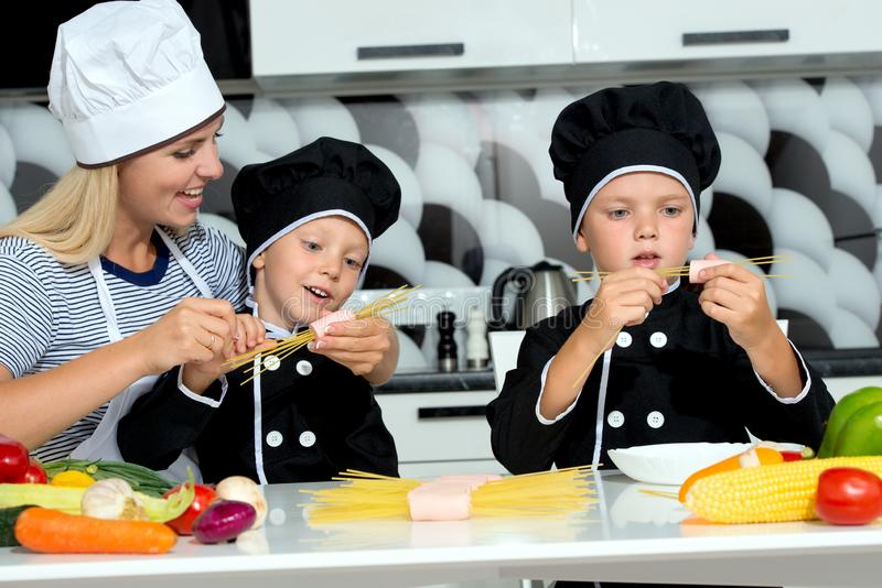 A family of cooks.Mother and children prepares spaghetti in kitchen. Delicious Spaghetti royalty free stock image