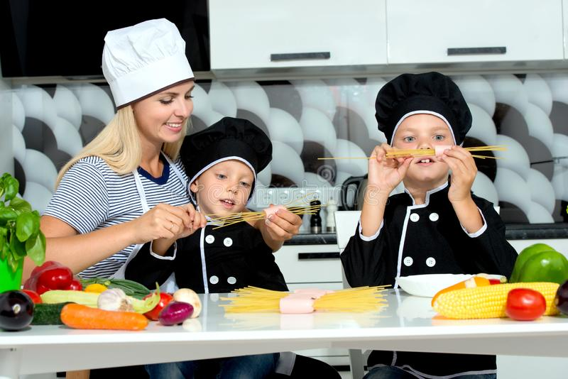 A family of cooks.Mother and children prepares spaghetti in kitchen. Homemade food royalty free stock images