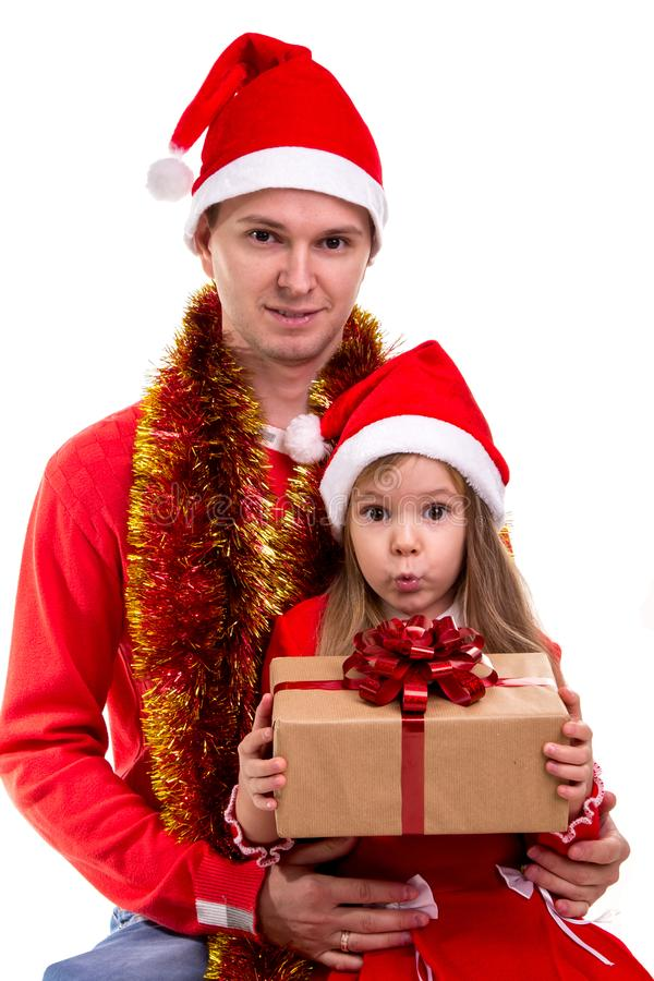 Family cosy xmas time. Daughter sits on the fathers knees holding a gift box. Daughter and father wearing santa hats and. Family cosy xmas time. Daughter sits on royalty free stock photography