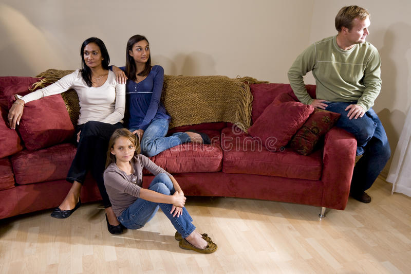 Family on couch with father sitting apart royalty free stock image